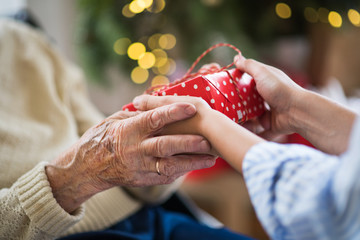 Close-up of hands of senior and young woman holding a present at Christmas.