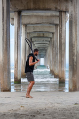 Athletic Man Jumping Rope at the Beach Under the Pier