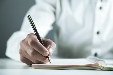 Businessman writing on a notepad in business desk.