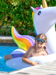 Boy swimming on unicorn float