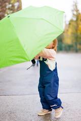 Little child playing with umbrella. Kleines Kind spielt mit Regenschirm.