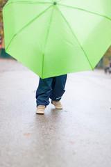 Little kid with green umbrella on wet road. Kleines Kind spielt mit grünem Regenschirm auf nasser Straße.