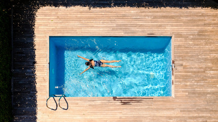 Anonymous woman swimming in pool
