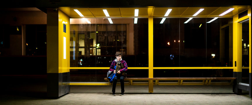 young man sit on the bus stop bench waiting in the night f