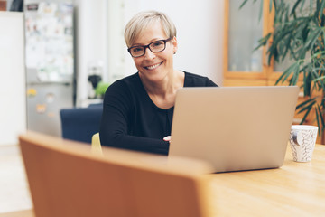 Middle-aged blond woman using a laptop