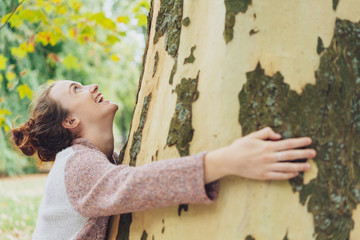 Laughing happy young woman hugging a tree
