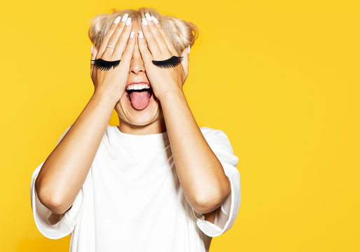 Attractive girl with eyelash on hands. Blonde cool model at studio on yellow background. Funny photo shoot concept.