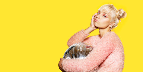 Portrait of lovely bored blonde young female in fluffy trendy sweater holding silver disco ball. Party and fashion concept. Isolated on yellow background