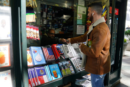 "A man makes a purchase at a news stand outfitted with ""Fake News"" headlines for a stunt pulled off by the Columbia Journalism Review in the Manhattan borough of New York, New York"