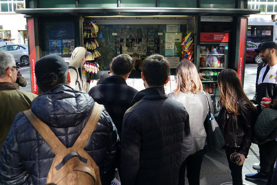 "People look at a news stand outfitted with ""Fake News"" as a stunt pulled off by the Columbia Journalism Review in the Manhattan borough of New York"