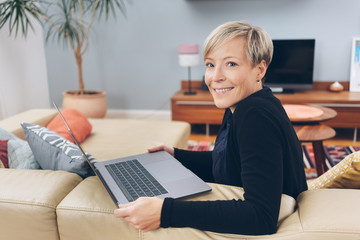 Attractive woman relaxing at home with a laptop