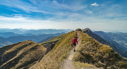 nice senior woman, hiking in fall, autumn  on the ridge of the Nagelfluh chain near Oberstaufen, Allgaeu Area, Bavaria, Germany, Hochgrats summit in the background Wall mural