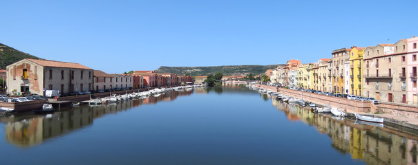 Panorama of the Temo river with colourful houses reflecting in the blue water, Bosa, Sardinia, Italy