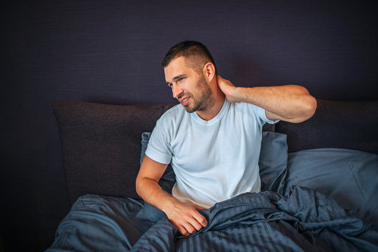 Young man sits on bed and feels pain in neck area. He shrinks and looks to left. Guy holds hand on neck behind. He is partly covered with blanket.
