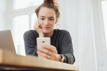 Young businesswoman reading a text message