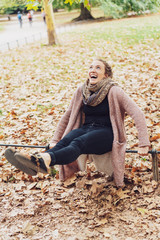 Carefree young woman in an autumn park