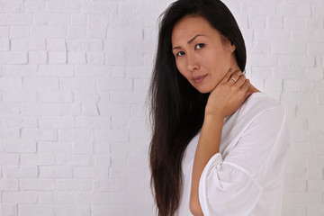 Asian Woman suffering from neck and back pain. Incorrect sitting posture problems, Muscle spasm, rheumatism. Pain relief, chiropractic concept.