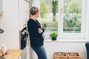 Woman daydreaming leaning on a kitchen cabinet
