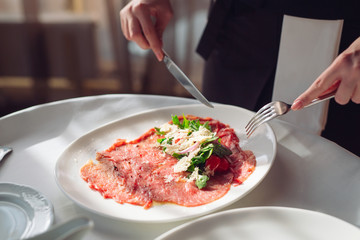 Red beef carpaccio in a white plate,