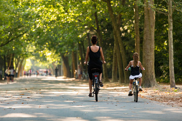 A woman and a girl biking in a sunny Amsterdam Vondelpark in the Netherlands.