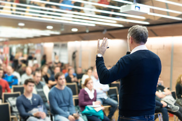 Expert giving a talk on business conference workshop. Unrecognizable people in audience at the conference hall. Business and entrepreneurship event.