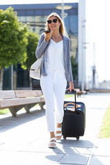 Beautiful young businesswoman talking on the smartphone while walking with suitcase in the street.