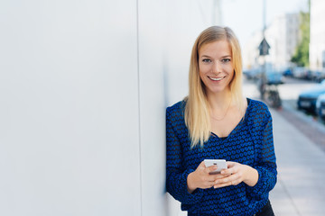 Smiling young woman holding her mobile phone