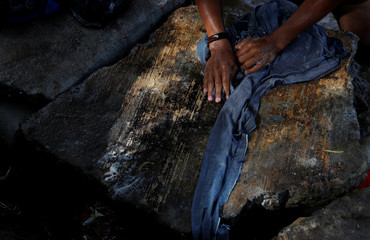 A migrant washes his pants in the river a day after the caravan he is part of was stopped at the border in Ciudad Tecun Uman, Guatemala