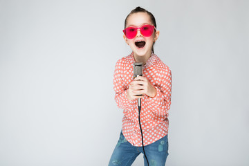 Girl on a gray background singing into the microphone.
