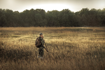 hunter hunting in  rural field nearby woodland at sunset during hunting season Wall mural