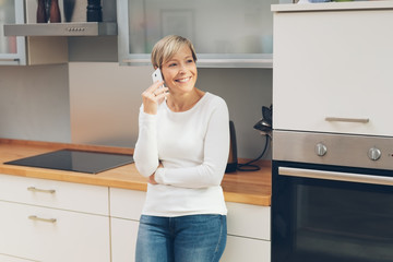 Housewife relaxing in the kitchen using a mobile