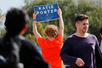 Supporters for Democratic congressional candidate Katie Porter, running in 45th Congressional District, point students to early voting booths at University of Irvine campus in Irvine, California