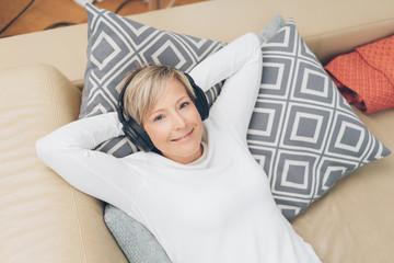 Blissful woman relaxing at home with her music
