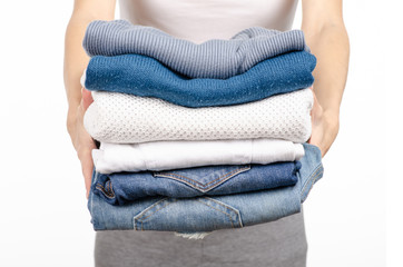 A stack of sweaters jeans in the hands of a woman on a white background. Isolation