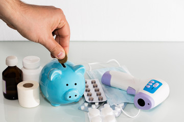 A piggy bank sits on top of pills to pay for rising drug prices. Health care