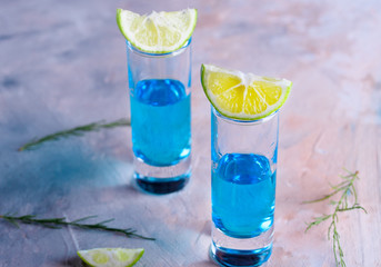 Delicious blue drink with a handful of green lemon. Cocktail with limnom concrete background. Blue cocktail with lemon.
