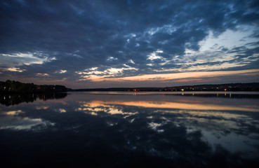 Beautiful sunset on the lake with reflection in the water surface.