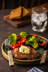 Grilled Beef steak with garlic butter and vegetables. Meat with grilled bell pepper, broccoli and onions.
