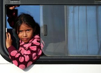 Isis Alexandra, an eight-year-old migrant girl from Honduras, travelling with a caravan of thousands from Central America en route to the United States, travels on a bus as she is transported to Juchitan from Santiago Niltipec