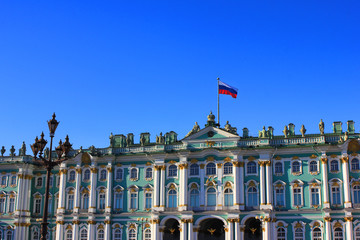 Winter Palace and Hermitage Museum Building at Palace Square in Saint Petersburg, Russia. Facade Architecture with Russian Flag of Old Historic City Landmark on Blue Sky Background on Summer Day