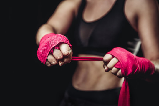 Woman wraps her fists in pink bandages for boxing gloves