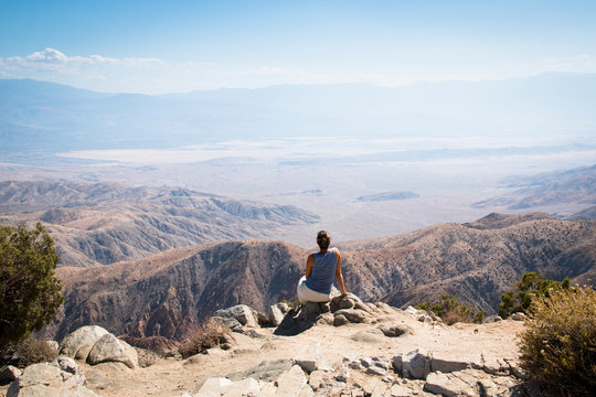 A girl viewing over Joshua Tree National Park with its typical trees and rock formations near Palm Springs in the California desert in the USA