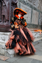 Carnival black-orange mask and costume at the traditional festival in Venice, Italy
