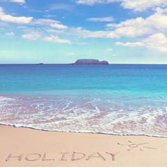 HOLIDAY insctiption under the sun drawing on wet beach sand with the turquoisesea and the island on background