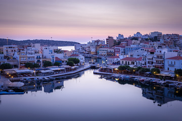 AGIOS NIKOLAOS, CRETE, GREECE - SEPTEMBER 8 2016: Lake Voulismeni with restaurants, shops and hotels near it at sunrise
