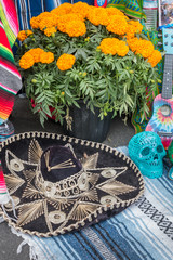 A very decorative sombrero, a pot of blooming marigolds and a neon blue skull form a memorial to the dead at a Mexican Day for the Dead memorial. All are on a Mexican blanket.