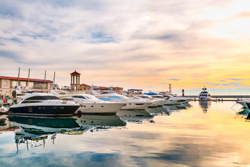 Luxury yachts at sunset. Marina of modern motor and sailing boats in sunshine. Reflection blue sky in water. Sea port dock. Travel and fashionable vacation.