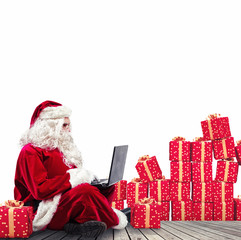 Technological Santa Claus sitting with laptop buys Christmas gifts with e-commerce
