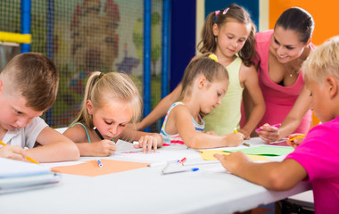 children sitting together and drawing in class at school