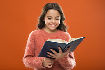 Useful information for her. Girl hold book read story over orange background. Child enjoy reading book. Book store concept. Wonderful free childrens books available to read. Childrens literature